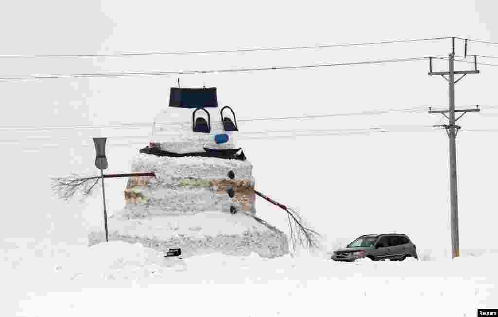 "A car passes a 50-foot snowman named ""Granddaddy"" in Gilman, Minnesota, USA, Mar. 6, 2014."