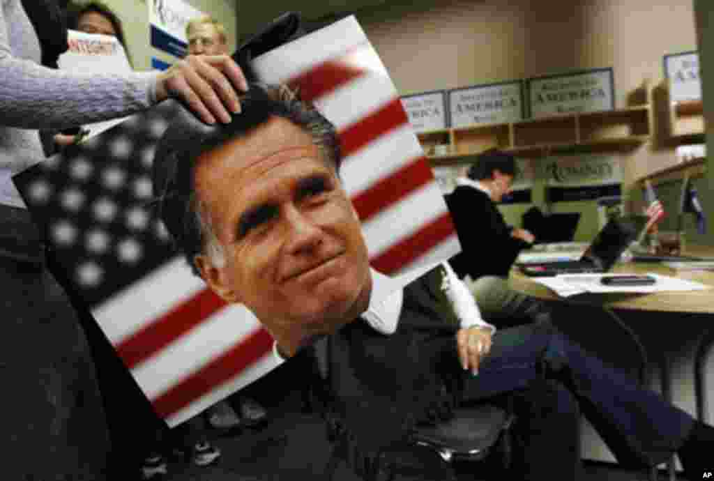 A supporter of U.S. Republican presidential candidate and former Massachusetts Governor Mitt Romney carries a photo of Romney past a campaign worker calling potential voters in Greenville, South Carolina, January 21, 2012. REUTERS/Jim Young (UNITED S