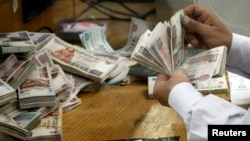 FILE - An employee counts money at a bank in Cairo, Egypt, Sept. 4, 2014.