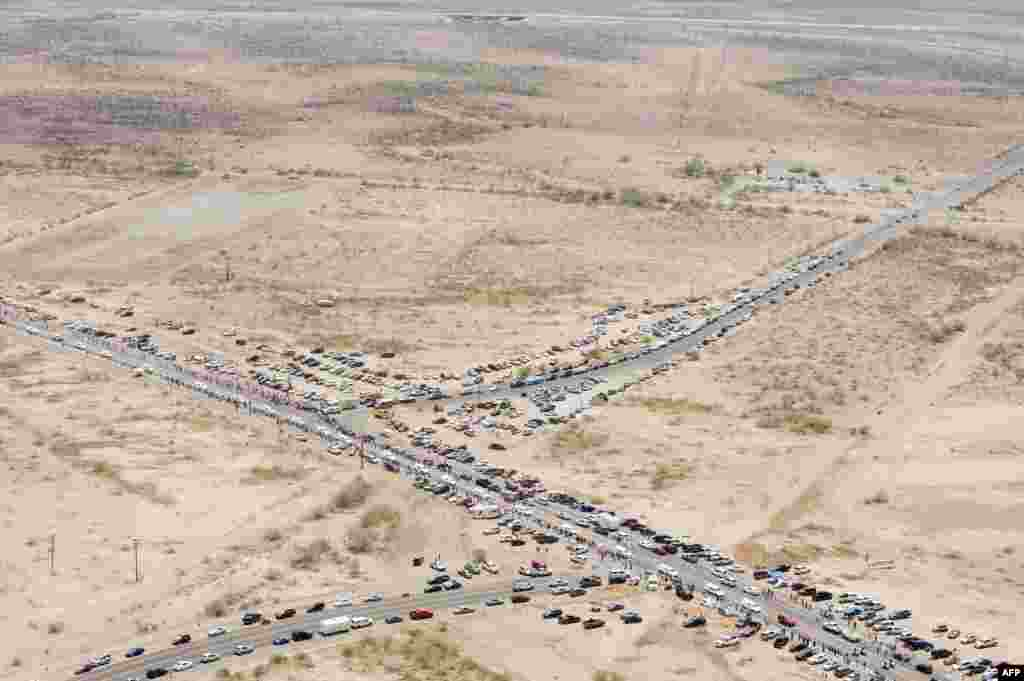 People gather along the side of the highway as the procession for the 19 fallen firefighters of the Granite Mountain Hotshots crew makes its way to Prescott in Phoenix, Arizona, USA, July 7, 2013. 19 of the 20-member crew died battling a fast-moving wildfire near Yarnell, Arizona on June 30.