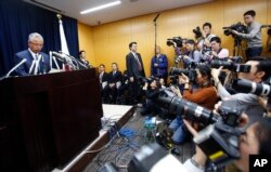 Japanese Economy Minister Akira Amari (l) speaks during a nationally televised news conference in Tokyo, Jan. 28, 2016.