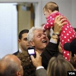 Mantan Presiden Clinton mengangkat seorang bayi saat berkampanye bagi kandidat John Hall di Harriman, New York.