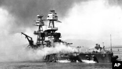 FILE - In this file image provided by the U.S. Navy, crewmen of the USS Nevada still fight flames on the battleship, battered in the Japanese aerial attack on Pearl Harbor on Dec. 7, 1941.