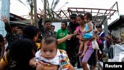 Binh sĩ giúp cư dân lên máy bay vận tải C130 của Mỹ, rời thành phố Tacloban bị bão tàn phá, ngày 11/11/2013.