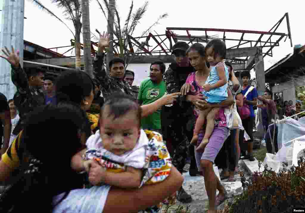 Tentara membantu warga naik pesawat militer AS C130 yang akan membawa mereka ke Manila, menyusul topan Haiyan yang menghantam kota Tacloban di Filipina tengah (11/11). (Reuters/Edgar Su)