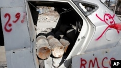FILE - Bombs inside a vehicle used by the Islamic State militants in suicide car bombings are pictured after a demining team defused them in Raqqa, Syria.