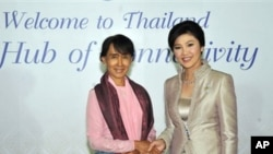 Burma's Aung San Suu Kyi, left, shakes hands with Thailand's Prime Minister Yingluck Shinawatra in this picture from the Thai government.