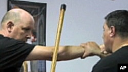 埃尔南德斯(右)向学员示范拐杖功招式