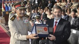 Egyptian President Mohamed Morsi, right, presented with gift from Field Marshal Mohamed Tantawi, former head of  SCAF, Hikstep, June 30, 2012.