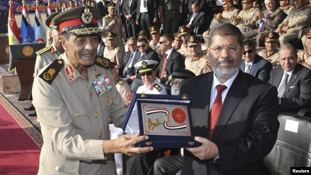 Egypt's new President Mohamed Morsi (R) poses with a gift from Field Marshal Mohamed Tantawi (L), head of Egypt's ruling Supreme Council of the Armed Forces (SCAF), during a ceremony where the military handed over power to Morsi at a military base in Hiks