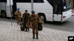 Members of the Organization for Security and Cooperation in Europe (OSCE) mission exit a bus for a hotel in Donetsk, Ukraine, March 12, 2014.