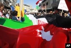 约旦抗议者2月8日挥舞着一面巨大的国旗