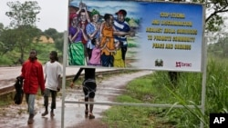 FILE - People walk past a billboard warning residents to stop the stigmatization of Ebola survivors, in Kenema, eastern Sierra Leone, Aug. 12, 2015.