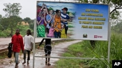 FILE - People walk past a billboard warning residents to stop the stigmatization of Ebola survivors, in Kenema, eastern Sierra Leone. On Nov. 7, WHO will declare the country is Ebola-free after going 42 days without any new infections.