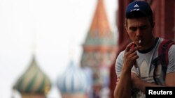 FILE - A man smokes a cigarette at Moscow's Red Square.