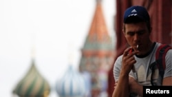 A man smokes a cigarette at Moscow's Red Square June 1, 2013. Russia has banned smoking at schools and universities, museums, sports facilities, hospitals and on public transportation. (FILE PHOTO)