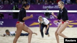 Kerri Walsh Jennings (R) and Misty May-Treanor of the US celebrate a point against Australia during women's beach volleyball match at 2012 Olympics