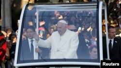 Paus Fransiskus melambaikan tangannya ke arah kerumunan warga yang memadati jalanan saat meninggalkan ibukota Meksiko menuju Ciudad Juarez (17/2).