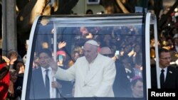 Pope Francis waves to the crowd as he leaves the capital en route to Ciudad Juarez, the last stop of his visit to Mexico, in Mexico City, February 17, 2016.