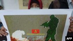 Seorang demonstran menunjukkan poster penculikan aktivis pada 1997-1998 dalam unjuk rasa memprotes pencalonan Prabowo Subianto dalam pilpres 2014, 20 Mei 2014. (Foto: AFP)