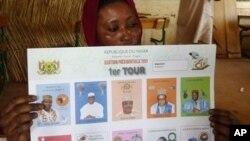 Wata mace take rike da katin kuri'a a wata rumfar zabe a Niamey,babban birnin Nijar.