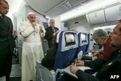 FILE - Pope Francis speaks to journalists aboard the flight from Mexico to Italy, on Feb. 18, 2016.