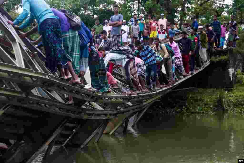 People cross a broken bridge in Sylhet, Bangladesh, July 7, 2019.