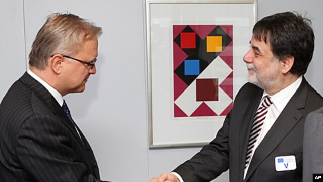 Hungary's chief negotiator with the IMF and the EU, Tamas Fellegi, right, shakes hands with European Commissioner for Economic and Monetary Affairs Olli Rehn, left, in Brussels, January 20, 2012.
