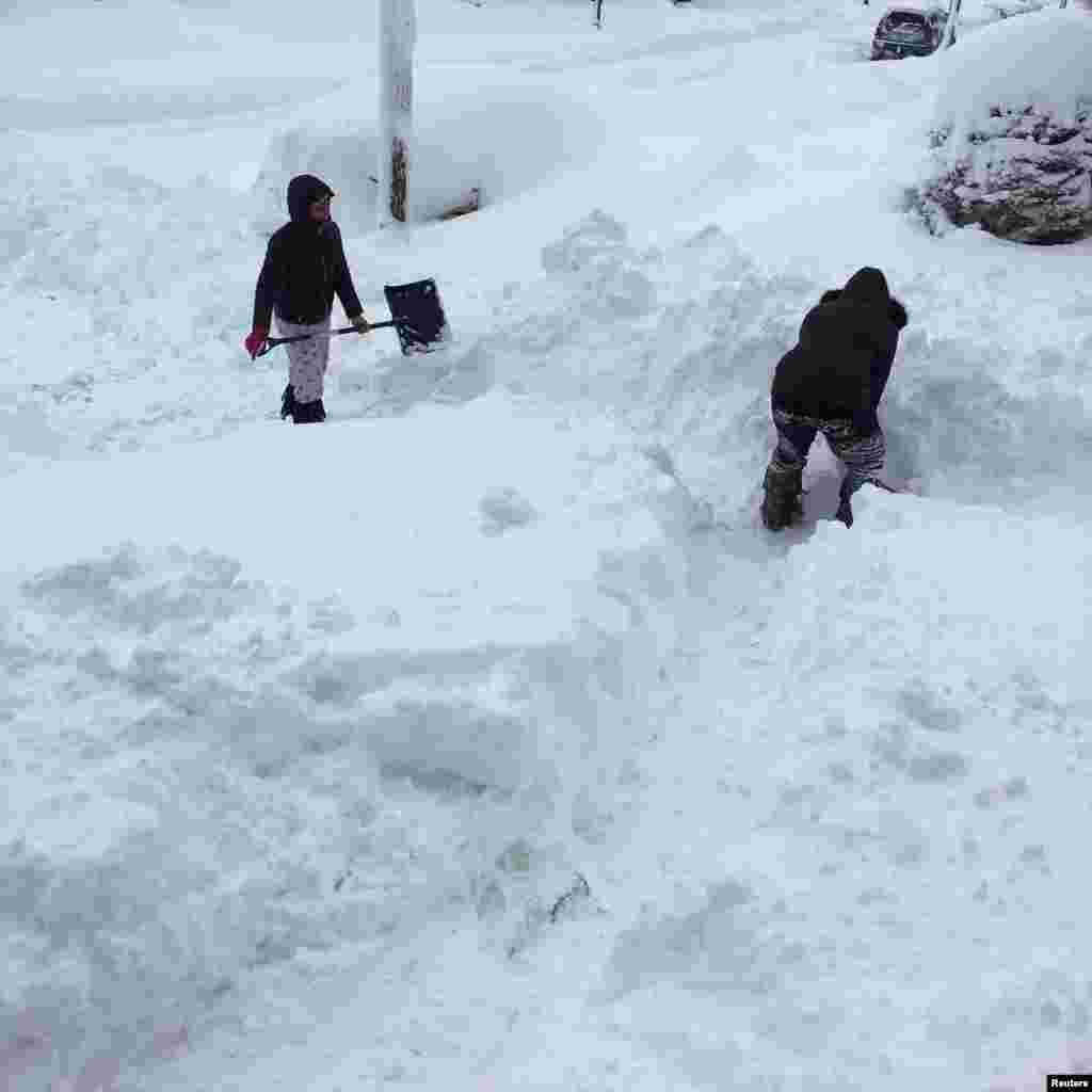 People dig out the path by their house after the record snowfall in Erie, U.S. in this picture obtained from social media. Courtesy of Instagram @DANIELLESOFANCY /via REUTERS
