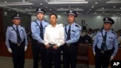 Mantan anggota tertinggi Partai Komunis China, Bo Xilai, diborgol dan dikawal oleh polisi saat berdiri di pengadilan di Jinan, provinsi Shandong, China, 22 September 2013 (Foto: dok).