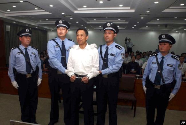 济南市中级人民法院发布的照片显示, 2013年9月22日,带上手铐的薄熙来被法警押上法庭,出庭受审。
