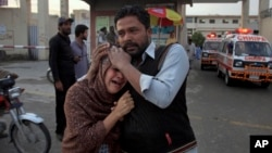 A man comforts a Christian woman who lost her husband in a deadly shooting incident, outside a hospital in Quetta, Pakistan, April 15, 2018.