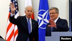 U.S. Vice President Joe Biden (L) waves as he meets Polish President Bronislaw Komorowski in Warsaw, March 18, 2014.