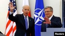 U.S. Vice President Joe Biden (L) waves as he meets Polish President Bronislaw Komorowski in Warsaw, March 18, 2014.