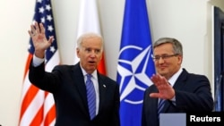 U.S. Vice President Joe Biden (L) waves as he meets Polish President Bronislaw Komorowski in Warsaw March 18, 2014.