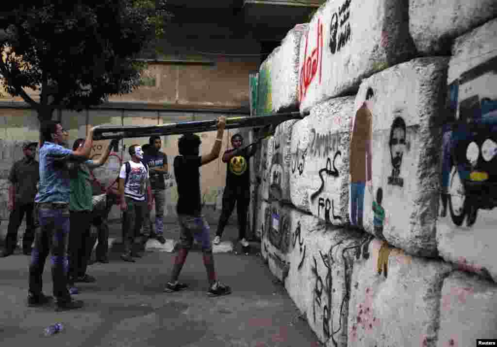 Activists attempt to remove a block from a wall blocking passage to parliament near Tahrir square, Cairo, Egypt, July 10, 2012.