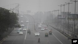 Vehicles move through morning smog on the last day of a two-week experiment to reduce the number of cars to fight pollution in New Delhi, India, Jan. 15, 2016.