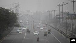 Seorang perempuan India menyeberang jalan di tengah kabut asap atau smog di New Delhi.