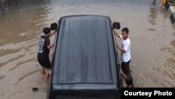 Warga mendorong mobil yang mogok terendam banjir di Karawang, Jawa Barat. (Foto: Dok)