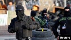 تظاهرکنندگان طرفدار روسیه با نقاب از ساختمان دولتی که اشغال کرده اند حفاظت می کنند - دونستک، شرق اوکراین