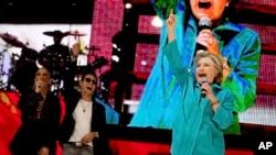ຜູ້ລົງແຂ່ງຂັນເອົາຕຳແໜ່ງປະທານາທິບໍດີ ທ່ານນາງ Hillary Clinton, ພ້ອມກັບນັກຮ້ອງຊື່ດັ່ງ ນາງ Jennifer Lopez, ຊ້າຍ, ແລະ ນັກຂຽນເພງທ່ານ Marc Anthony, ທີສອງ ຈາກຊ້າຍ, ກ່າວໃນງານສະແດງ ອອກມາເພື່ອລົງຄະແນນສຽງ ທີ່ໂຮງລະຄອນ Amphitheater ສວນ Bayfront, ເມືອງ Miami, 29 ຕຸລາ, 2016.