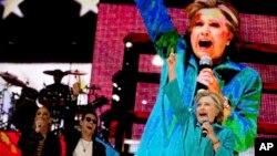 Calon presiden AS dari Partai Demokrat, Hillary Clinton, didampingi penyanyi Jennifer Lopez dan Marc Anthony, di atas panggung konser Get Out The Vote di Bayfront Park Amphitheater, Miami (29/10). (AP/Andrew Harnik)