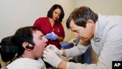 Jason DiSanto mendapat tindikan di lidah di Georgia Tech di Atlanta, untuk memasukan alat seperti perhiasan yang dapat mengendalikan kursi rodanya. (AP/Georgia Tech)