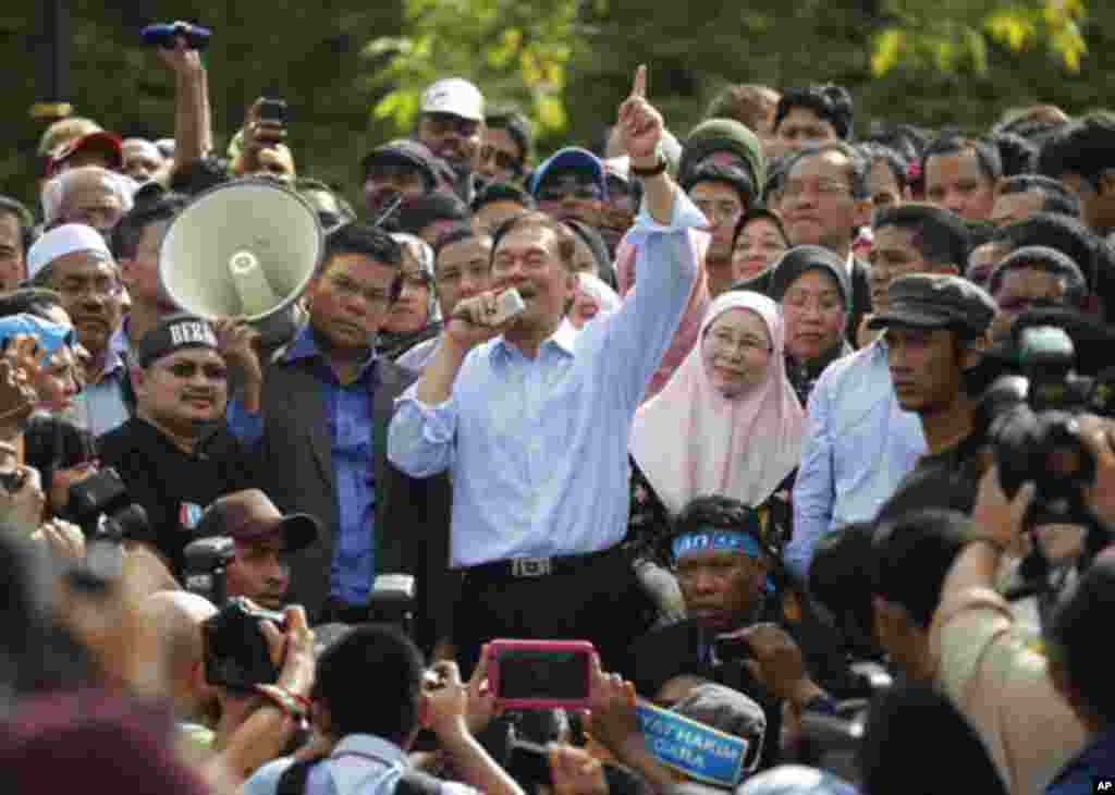 Malaysia's opposition leader Anwar Ibrahim (C) talks to his supporters while flanked by his wife Wan Azizah Wan Ismail after the verdict of his sodomy trial was announced in Kuala Lumpur January 9, 2012.
