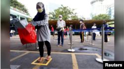 Warga Jakarta mengenakan masker saat antre untuk menerima pembagian beras saat pemberlakuan PSBB di DKI Jakarta.