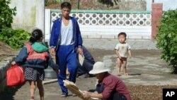 图为北韩农民在集体农庄晾干粮食的资料照