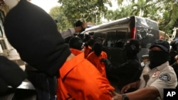 Police anti-terror unit escort suspected militants before a press conference in Jakarta, May 17, 2019. Police say they have arrested suspected militants following a tipoff about a possible attack during the announcement of presidential election results next week.