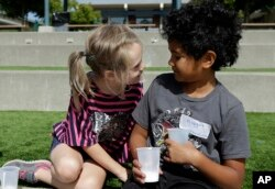 FILE - Camper Gracie, left, leans toward Nugget during an activity at the Bay Area Rainbow Day Camp in El Cerrito, Calif., July 11, 2017.