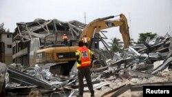 Un secouriste se tient sur des gravats d'un immeuble effondré dans le district de l'île Victoria à Lagos, Nigeria, 5 novembre 2013
