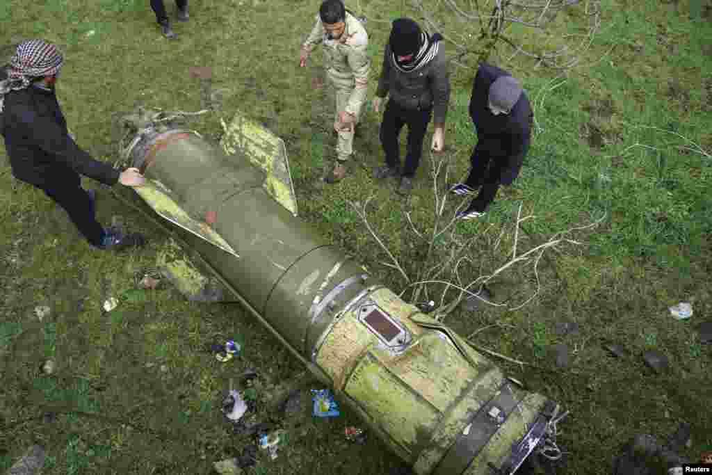 شورشیان یک تکه از راکتی که در بخشی از درعا در سوریه افتاده را بازرسی می کنند.